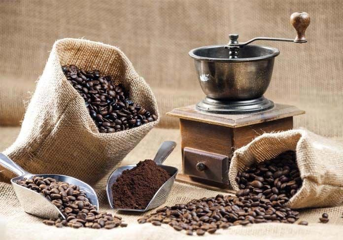Bags of coffee beans and an old coffee grinder with a handle on top.