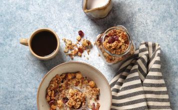 Bowl of granola with black coffee and jug of milk