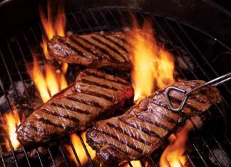 Steaks getting cooked over flames