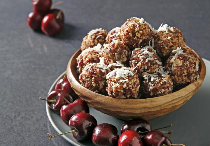 A bowl of energy balls sitting on a plate with cherries around it